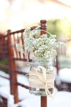 Ogni sedia è decorata da un semplice barattolo appeso con del fil di ferro, un nastro rosa e dei fiori di campo.