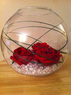 Gallery item: Rose fishbowl centrepiece<br /><p>Goldfish bowl filled with crystals, grasses and 3 red roses placed on top. An e-luminator or individual lights can be added to the bowl which is then placed on a mirror</p>