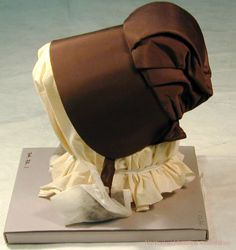 """Dark gray-brown Quaker-style bonnet with ribbon ties. Crown has center pleat with two smaller pleats on each side. 2"""" apron. Silk and buckram lining. NHA 1974.0072.001"""