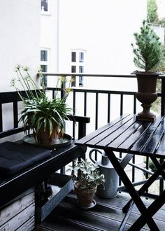 Sleek black furniture and deep green plants give this Nordic style balcony a  modern vibe.