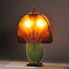 Art Deco Table Lamp  Mica, glass, metal, enamel  Probably France, c. 1920  Shade composed of mica panels enameled with abstract geometric sun motif, over a double socket raised on a green crackle glass base with cast metal scrolled foot.