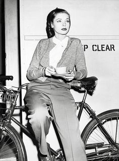 Lauren Bacall taking a tea break while sitting on a bike n a pair of creased trousers. #vintage #1940s #actresses