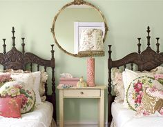 In the guest room, Elizabeth livens a pair of dark carved oak beds with a tumble of colorful pillows she created from her stash of fabrics. She updated the vintage floral theme by mixing in Ralph Lauren bedding and new lampshades from Anthropologie, a regular source for Elizabeth for vintage-inspired accents.