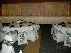 white drapery/lights backdrop for head table, white chair covers, black damask on white chair sashes Wedding Decorations, Wedding Ideas, Table Decorations, White Chair Covers, Black Weddings, Damask Wedding, Chair Sashes, Wedding Rentals, Event Decor