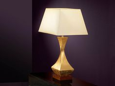 Table lamp of 1 light made of wood and metal. Silver leaves finish and very dark brown wooden square base.