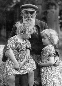 Großvater mit seinen Enkelkindern, 1936 Timeline Classics/Timeline Images #1930er #1930ies #Großvater #Enkelkinder #blonde #Mädchen #Alter #Kinder #alt #young #jung #old #historical #historisch #Blumenkleider #Sommerkleider #Generationen #Nachkommenm #Opa