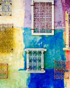 Lots of old scrolled metal window shutters on wall painted various bold colors..dramatic