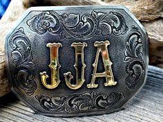 The Western custom belt buckle, personalized with initials in brass overlay and engraved rope border. Hand engraved with gun scroll style deep relief engraving. Available with your choice of shapes. Bluegrass Engraving.