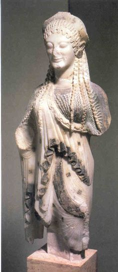 Acropolis Kore, (Ancient Greek Teenager), 530 BCE. She wears a chiton, the lower garment with the wavy folds, under a heavy shawl-like epiblema. On her head is a curved tiara called a stephane.  These statues are known for their ornately patterned hair, accessories, and archaic smiles.