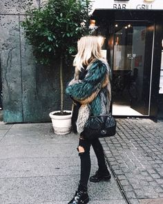Multicolor fur with Chanel, ripped black jeans, and boots.