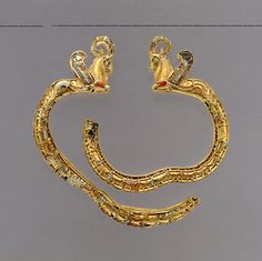 Pair of Achaemenid Gold Bracelets with Winged-caprid Termini with Cloisonne Inlay, mid 6th-4th century BCE. Gold with lapis lazuli and carnelian inlay.