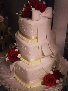 3 tier heart shaped wedding cake is covered in a soft ivory colored fondant. Adorned with contrasting ivory hearts, soft ivory bows and gumpaste roses. The cake is layers of white cake with white chocolate ganache and fresh raspberries as the filling and the fondant is also raspberry flavored.