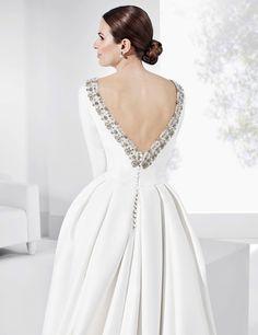 Traje de novia de corte clásico con galón de escote y puños plateados.