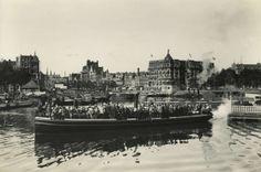 Het bootje van de Noord-Hollandse Tram brengt mensen, die op weg zijn naar Marken of Volendam, naar de overkant van het IJ.  Op de achtergro...