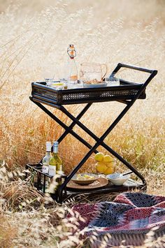 black rattan bar cart in field #picnic #woven blanket #outdoor entertaining