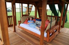 Redwood Daybed swing installed under a massive Fort Ticonderoga playset. Kids Backyard Playground, Backyard For Kids, Backyard Projects, Outdoor Daybed, Outdoor Decor, Outdoor Ideas, Patio Under Decks, Outdoor Swing Sets, Outdoor Play