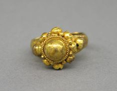 Ring with Large Central Boss Flanked by Series of Same