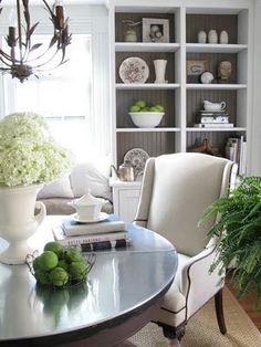 love the feel.  backs of the built-ins, round table, chair, hardwood with a jute rug, chandy, pops of green.