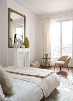 All-white bedroom with crown mouldings, carved marble fireplace and gilded mirror.