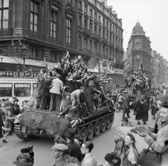 Civilians ride on Cromwell tanks as the British enter Brussels, 4 September 1944.