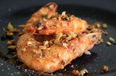 This recipe is for those of us who eat the entire shrimp. Toss just-fried shrimp with minced garlic, green onions, and red chili, all of which you have browned with a bit of oil. The garlic, green onions, and spices will cling to the shrimp. Sprinkle salt, pepper, and whatever other spices you like. The seasonings will stick pretty well to the shells, which are coated in a little egg and cornstarch or flour, but whatever does not cling to the shrimp will be fun to grab from the platter.