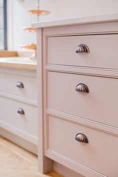 Chocolate bronze cup handles provide one of the finishing touches on this bespoke kitchen by Planet Furniture. Perfect against Little Green's Light Peach Blossom 3 paint colour.
