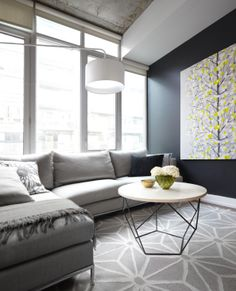 Contemporary condo living room with gray sofa, geometric area carpet and black feature wall - LUX Design