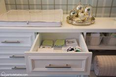 Cômoda com trocador de bebê com enxoval branca estampado e kit higiene prata.