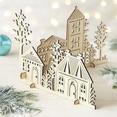 Set up a miniature village of laser-cut wood structures with charming architectural detailing and tree silhouettes.  Two sections piece together and stand on removable feet.  Create a winter wonderland with coordinating laser-cut trees and animals. PlywoodFor decorative use only; not a toyMade in China.