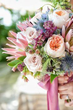 Exotic King Protea, Juliet Garden Roses, Astrantia, Poppy Pods, Agapanthus, Explosion Grass, Thistle, Leucadendron bouquet with silk ribbon....