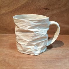 Horizontal Folds by Clementine Porcelain. This translucent porcelain cup is a *slip cast:slip casting* reproduction of a folded paper prototype. These are dishwasher and microwave safe