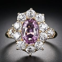 A fabulous, original antique treasure by America's formerly preeminent jeweler - Tiffany & Company. This thoroughly feminine and entrancing Edwardian ring, circa 1900, highlights a ravishing, passionate pink Topaz, classically presented in a sparkling diamond 'halo' - or in modern parlance - 'Lady Di' style setting. Ten old mine-cut diamonds glisten from graceful coronet settings and a single diamond on each shoulder transitions to a gently tapered knife-edge ring shank. Hand crafted in rich…