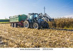 Biskupice Radlowskie, Poland - October 2, 2015: Branded tractor with a green trailer full of harvested corn stands in the field