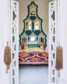 In the master bedroom, the bed of a Tuareg nomad is topped with a silk ikat coverlet from Uzbekistan and a Moroccan brocade pillow; the Tuareg door tassels are from Mauritania, and the mirrors are Syrian.