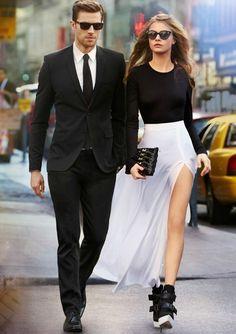 couple white long side slit skirt black long sleeves top heels sunglasses black suit tie new york city