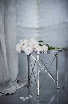 Ralph Lauren Home's polished steel, neoclassical Cannes Guéridon table paired with blooming white peonies