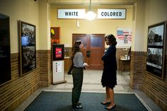 Perfect photo simultaneously acknowledges the progress America has made thus far and how far the country still has to go.  1st Lady speaking with a tour guide at Monroe Elementary School in Topeka, Kansas, the historical sight of Brown v. Board of Education.