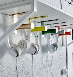 Cinq porte-rouleaux WC IKEA GRUNDTAL sont fixés en dessous d'une tablette et utilisés pour accrocher des écouteurs.