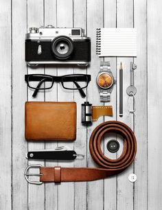A camera, a belt, a watch and a wallet in a flatlay style layout.Creative still life photography of fashion accessories.By luxury goods still life photographer London,Josh Caudwell. For product and editorial photography in London, New York, Paris, Milan.