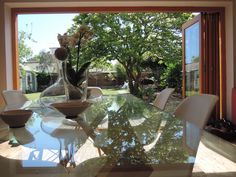 Habitat glass dining room table with pottery from Spain & France overlooking garden through oak bi-fold doors