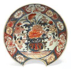 PLAT À BARBE en porcelaine décorée en bleu sous couverte, rouge de fer et émail or dit «Imari» d'un vase fleuri au centre, le bord à réserves de maisons (fêlure). Chine. Epoque Kangxi (1662-1722). D_29 cm