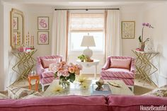 Living room curtains in Sahco's Linora are trimmed in a custom fabric to pick up the hues of the striped chairs. Angular consoles from Grey offset the femininity of pink accents and walls in Benjamin Moore's White Blush. The temple cocktail table is from Baker, while the orange side table is from Todd Alexander Romano.   - TownandCountryMag.com