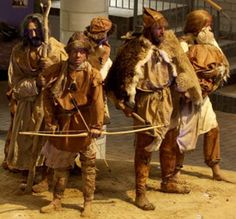 A group of recreated Neolithic men wearing naturally tanned animal hides.