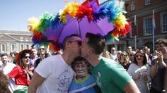Two men kiss in front of cardboard cutout of popular Irish television character Mrs Brown