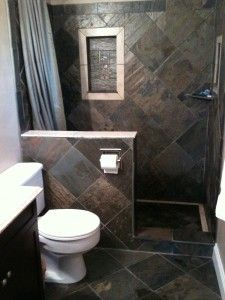 Slate tiles with a travertine inset between the studs and a pre-fab vanity with granite counter transform this 1970s bathroom into an elegan...
