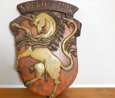 "The phrase across the top, Spero Melior, is Latin for ""I hope for better things."" Don't we all!   Vintage Hand Carved Wood Unicorn Coat of Arms by SadieBessVintage, $495.00"