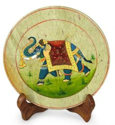 "Royal Elephant : Hand painted Soapstone plate with a stand  A royal elephant in scarlet silk strolls through a  green meadow  Product Code : PL-01  Size :   Plate: 0.2"" H x 6"" Diam.  Stand: 4.9"" H x 3.9"" W x 2.8"" D  Weight: 0.7 lbs"