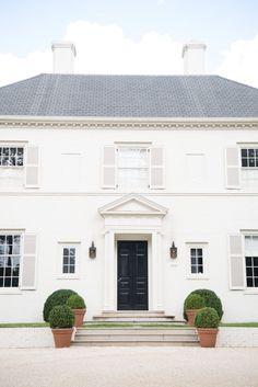 gray roof, two chimneys, double chimneys, boxwood, terra cotta pots, white shutters, white brick, black door, gravel