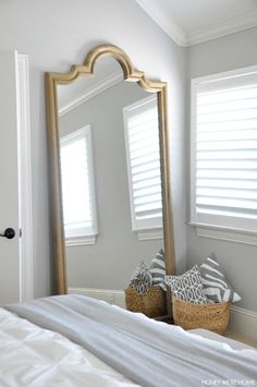 neutral master bedroom, full size leaning mirror w/wicker basket holding gray and white pillows