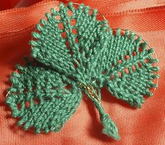 Ravelry: Anti-Pinch Shamrock Pin pattern by Lara Neel. She runs a bit of wire through the edges for shaping, instead of binding off.